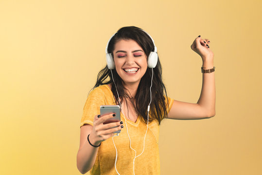 Young woman listening music with smartphone on yellow background