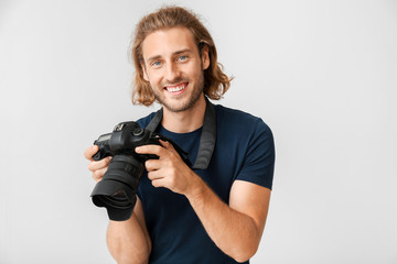 Young male photographer on light background
