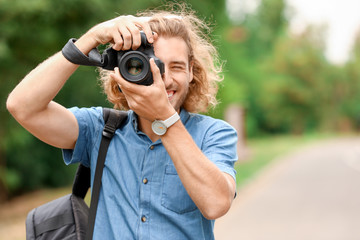 Young male photographer with camera outdoors Fotobehang