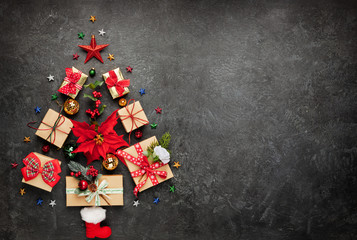 Christmas tree made from Christmas gifts and decorations on black background. Creative winter holiday concept. Flat lay.