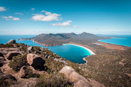 View from Mount Amos to the spectacular Wineglass Bay, white sandy beach and turquoise blue water, Freycinet National Park, Coles Bay, Tasmania, Australia