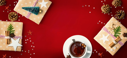 Wall Mural - Christmas gift boxes with a cup of tea - flat lay