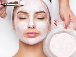 Fototapeta woman receiving  facial mask in spa beauty salon obraz