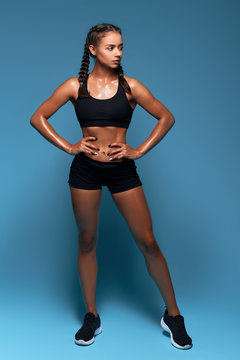 slim beautiful brunette woman with hands on the hips posing to the camera in the studio with blue wall, fitness, health and body care. full length photo
