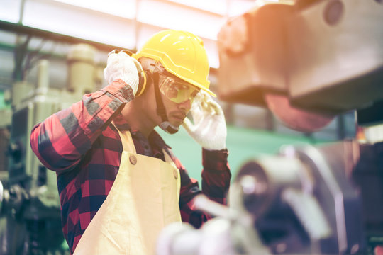 Manufacturer or Metal worker wearing safety glasses and protective helmets using lathe in order to machine or operating drilling machine concentrating on production plant job of production department