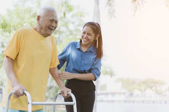 Portrait of happy female caregiver and senior man while using walker or Zimmer frame walking or exercise together at outdoor. Assisting the elderly or disabled Physiotherapy and Rehabilitation concept