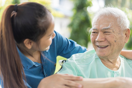 Happy Asian Grandfather or patient or elderly people in wheelchair .with granddaughter or caregiver spending time together. Love, Family or Assistant, Retirement, patient or elderly caregiver concept