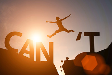 Obraz Silhouette man jump between can't wording and can wording on mountain. Mindset for career growth business. - fototapety do salonu