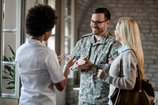 Happy military man and his wife talking to a doctor at medical clinic.