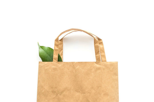 Recycled brown paper shopping bag with handle and green leaf isolated on white background. Zero waste. Top view, flat lay, copy space.