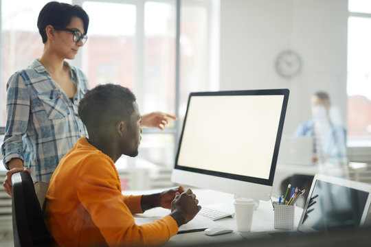 Side view portrait of two modern young people looking at blank white computer screen while working on startup project in office, copy space