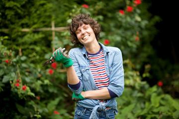 laughing female gardener standing with scissors in garden