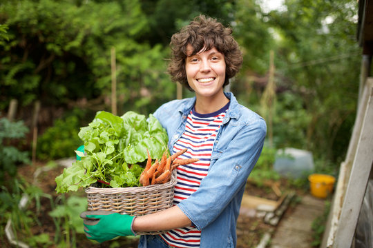 smiling farmer with bunch of vegetables in basket
