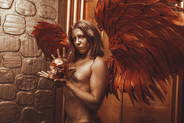 halloween make up. boy ready for party. man is covered in gold paint and poses with large angel wings and a skull in his hands against the backdrop of large doors in the Studio