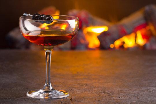 Manhattan cocktail on fireplace background