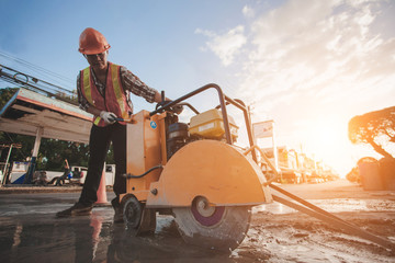 Construction worker cutting Asphalt paving stabs for sidewalk using a cut-off saw.