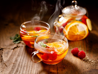 Fruit hot tea with the addition of oranges, lemons, mandarins and raspberries in a glass cups on a wooden table. Healthy hot drink