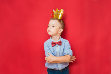 Emotional education and childhood concepts with an adorable 6-year old boy holding a golden king crown on his head as a wise spoiled child, red background
