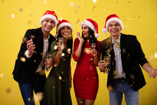 The best New Year ever. Two young couples in Christmas hats are having a New Year's Eve party, laughing with joy, cheering with glasses of champagne and throwing vivid confetti.