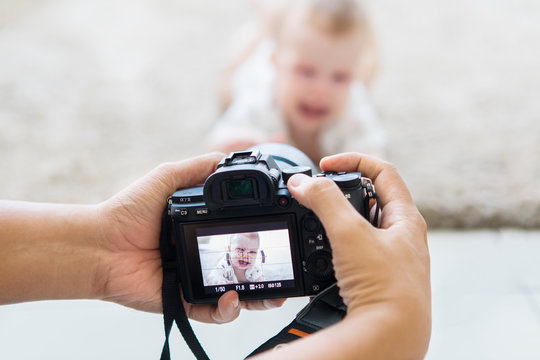 Hands of photographer take a photo of a cute baby