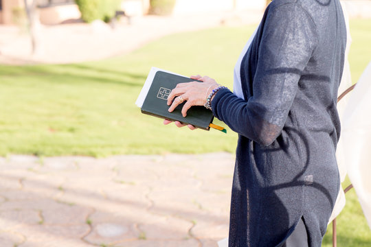 female minister preacher holding bible at wedding ceremony