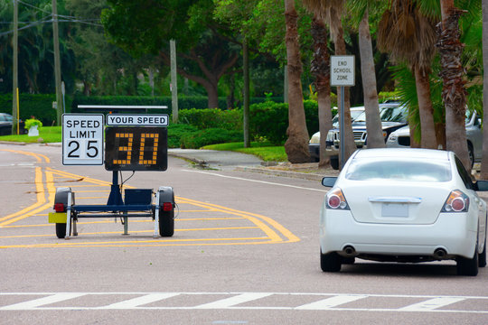 Radar speed limit indicator sign monitored by the police showing 30 miles per hour on the screen proving a passing car is speeding as it drives down the road in a clearly marked school zone.