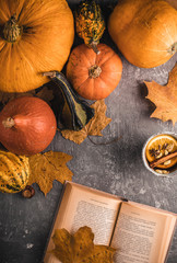 Relaxing moments with a hot beverage and book in the autumn arrangement full of pumpkins and maple leaves on the table.