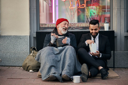 Stylish office worker and beggar male sit eating on street and speaking. Man un tuxedo, poor male in old clothes