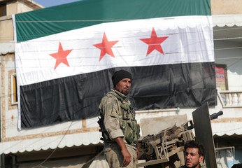 A Turkey-backed Syrian rebel fighter stands at a back of a truck, as the Syrian opposition flag is seen in the background, in the border town of Tal Abyad