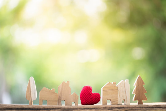 Red heart placed in the middle between the wooden house model put on the old wood on sunlight in the public park, Business investment or saving money to buy real estate for family concept.