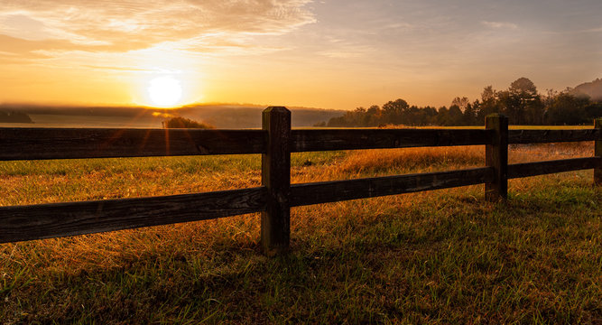 Split rail fence around North Carolina field at sunrise