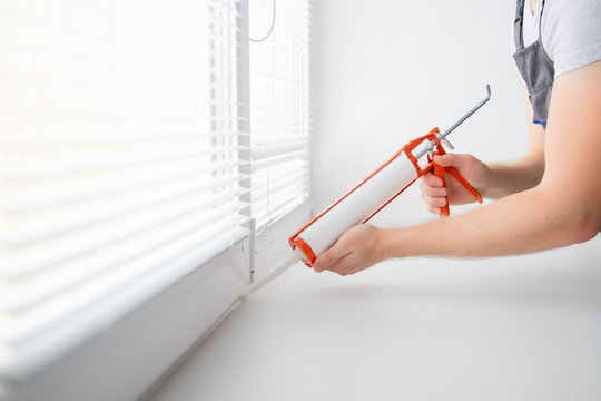 Construction worker use gun silicone tube for repairing and installing window in house