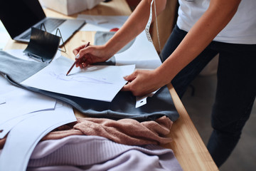 Making sketch for new fashion collection. Laptop, papers, textile on table
