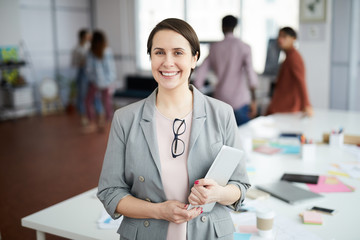 Waist up portrait of smiling businesswoman looking at camera and holding digital tablet while standing in modern office, copy space