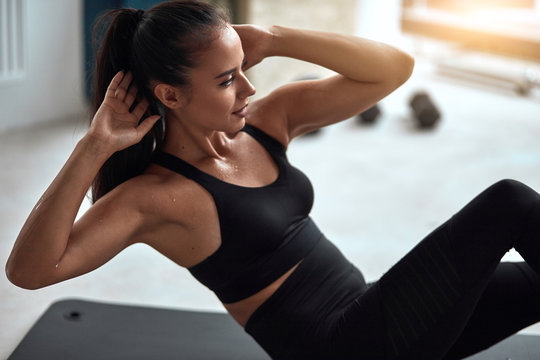 Attractive fit female pump press in gym. Fitness girl in black sportswear exercising