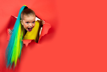 Back to school. Smiling funny child is breaking through color paper wall. Kid having fashionable haircut. Girl ready to school.