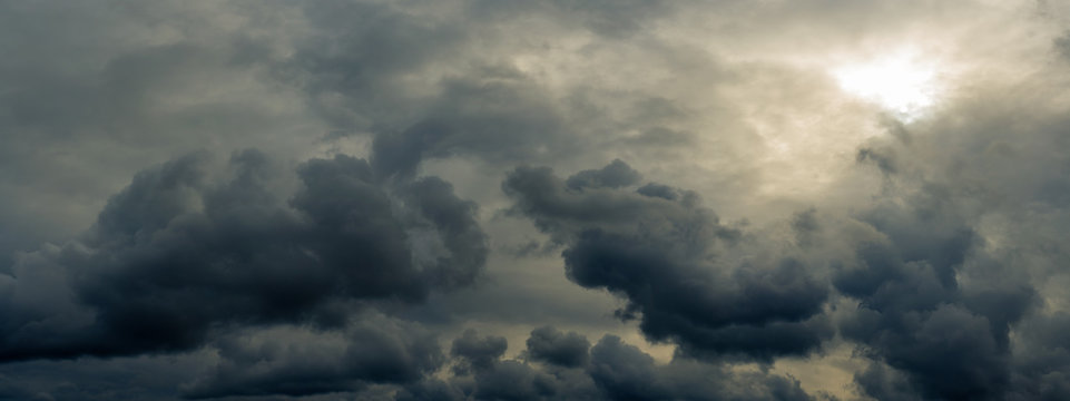 dramatic mystical sky with gray heavy clouds and faint back sunlight and lumen. artistic panoramic picture for the original background, layout or decoration