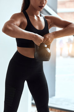 Young athletic and strong female holding, lifting up kettlebells with two hands. Sporty woman in black topic sportive wear in gym