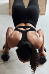 Top view on muscular female during push ups with dumbbells. Bodybuilding