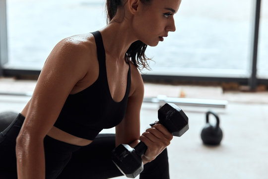 Sporty young female in black sportswear sit on fit box, dumbbells in hands.