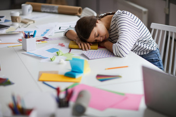 Side view portrait of young woman sleeping at desk exhausted from working or studying, copy space