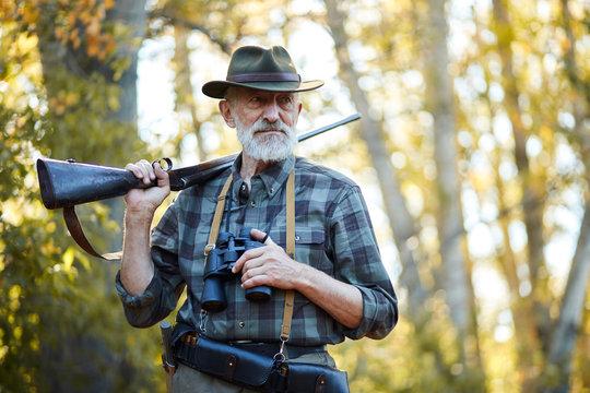 Senior hunter on birds holding gun on shoulder, straighten hat, looking away. Forest background