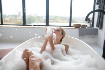 Obraz Blonde woman chilling in foamy bath having much fun - fototapety do salonu