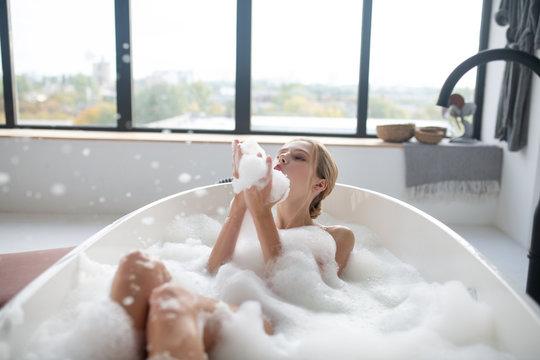 Blonde woman chilling in foamy bath having much fun