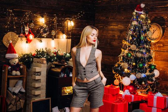 Beauty Christmas fashion model girl holding Christmas gift. Beautiful woman in Christmas clothing on Christmas tree background. Beauty Woman face Portrait.