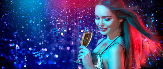 Model girl with glass of champagne drinking and dancing at disco party, on holiday glowing blue with red background. Beauty woman, perfect fashion makeup. Christmas and New Year holiday celebration