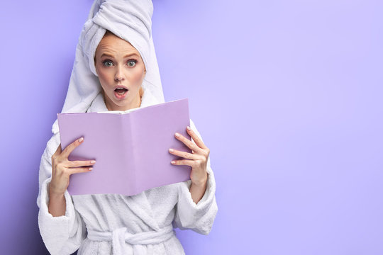 Caucasian woman wearing bathrobe and towel after shower reading book isolated over purple background. Emotions, reading