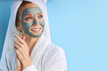 Female with perfect skin and natural make-up. Wearing bathrobe and towel after bathing, using mask. Isolated over blue background