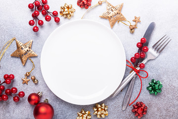 Christmas table place setting with empty white plate, cutlery with festive decorations star bow ball on stone background. Christmas and New Year holiday concept - Image