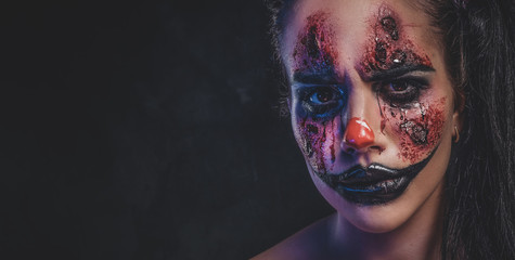 Pretty girl has very creepy makeup for Halloween in a role of creepy clown.